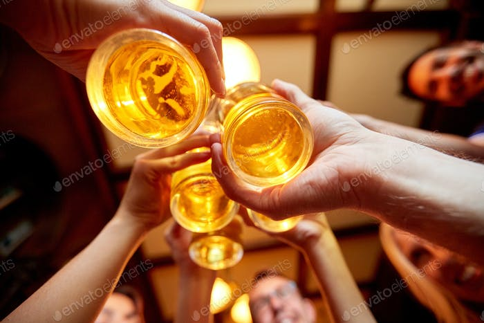 friends clinking beer glasses at pub or bar
