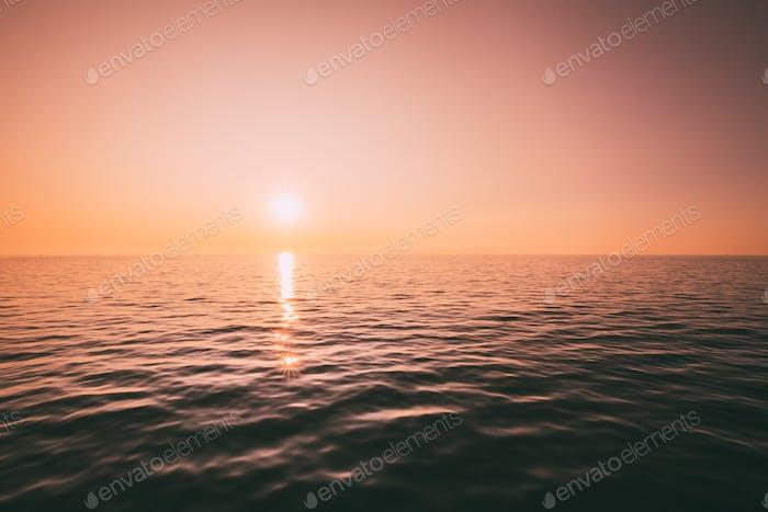 Sundown Above Sea Horizon At Sunset. Natural Sunrise Sky Warm Co