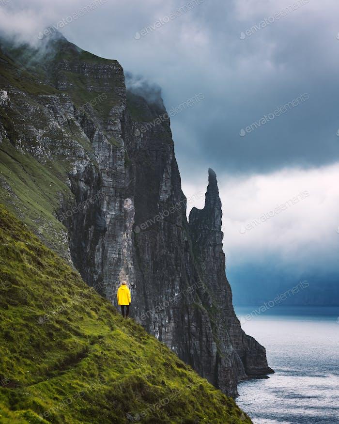 Tourist mit Rucksack in gelber Jacke sieht Witches Finger Klippen