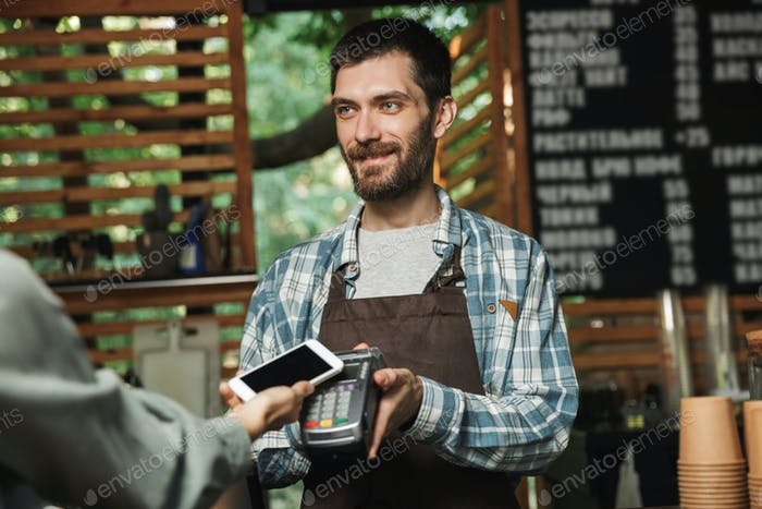 Portrait of friendly barista man holding consumer terminal for p