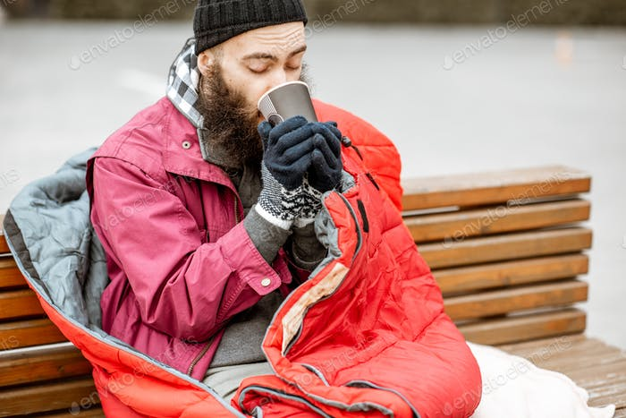 Beggar with hot drink outdoors