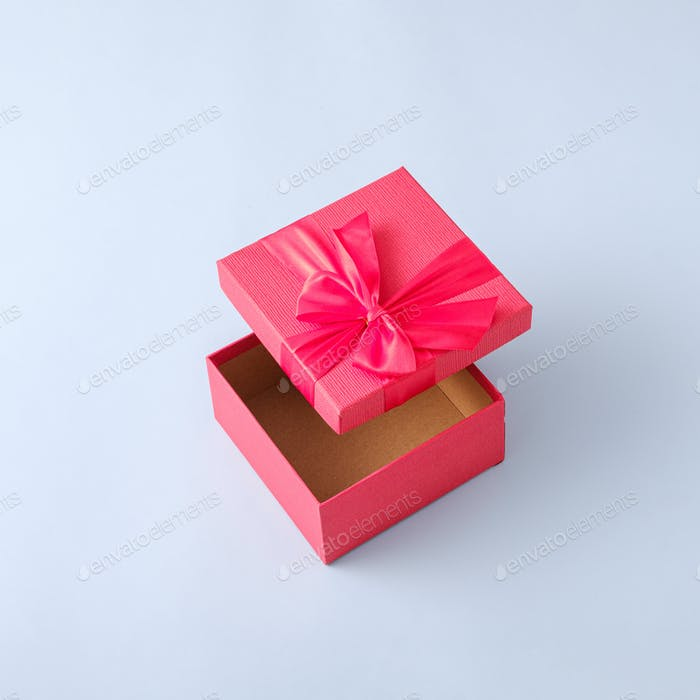 Surprise in a gift box with a ribbon. Minimal pastel concept with levitation of gift and event.