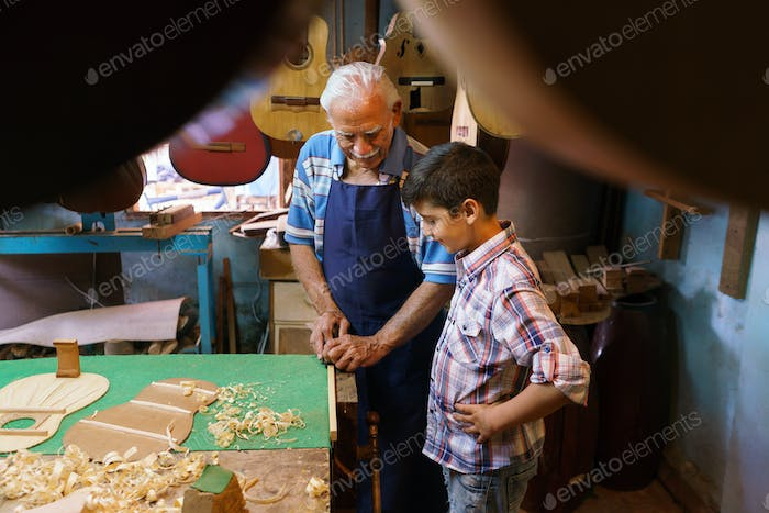 Old Lute Maker Teaching Grandson Boy Chiseling Wood