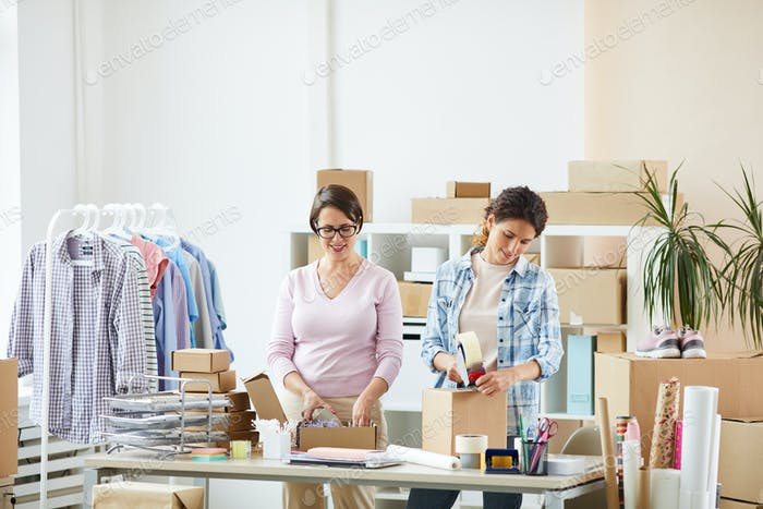 Young female colleagues standing by desk while making parcels for clients