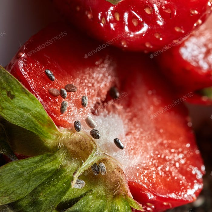 Close up of half of red ripe strawberry with seeds as a background