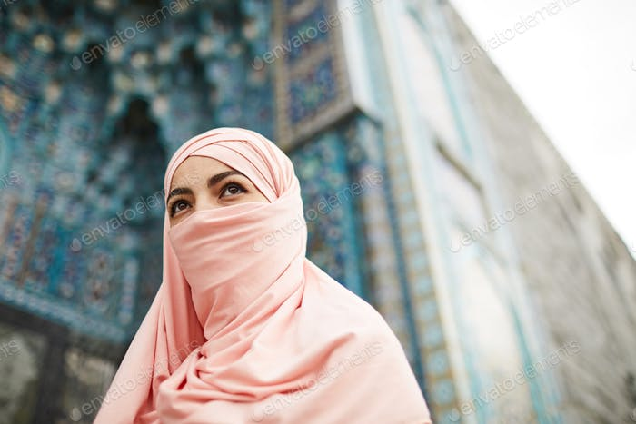 Muslim lady covering face with hijab