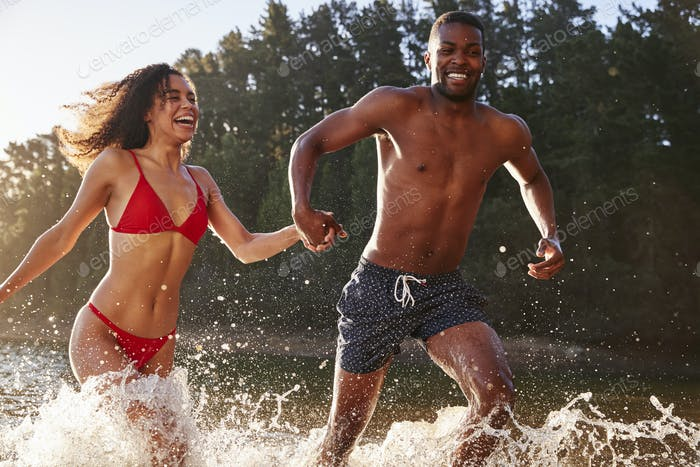 Young mixed race couple running and splashing in a lake