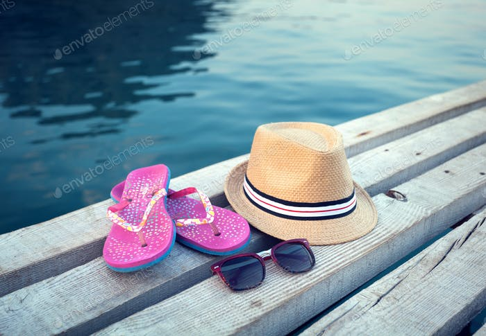 Sunglasses, flip-flops and hat on the wooden texture in summer