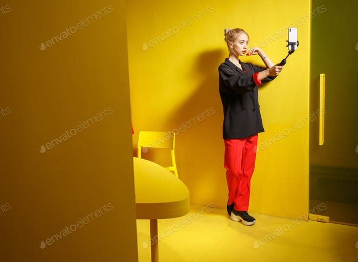 Fashion young girl blogger dressed in red trousers and black jacket takes a selfie on her smartphone