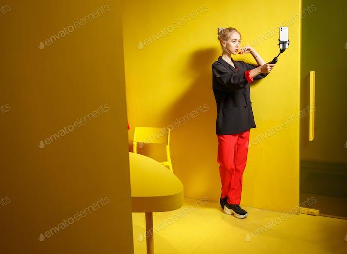 Mode junges Mädchen Blogger gekleidet in rote Hosen und schwarze Jacke nimmt ein selfie auf Ihr Smartphone