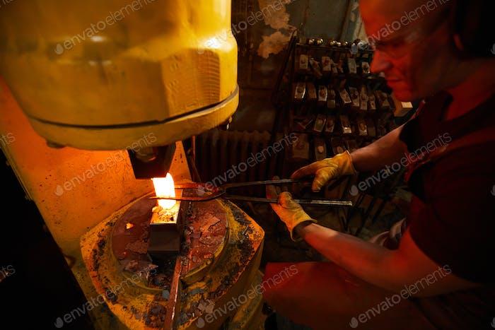 Pressing heated metal piece