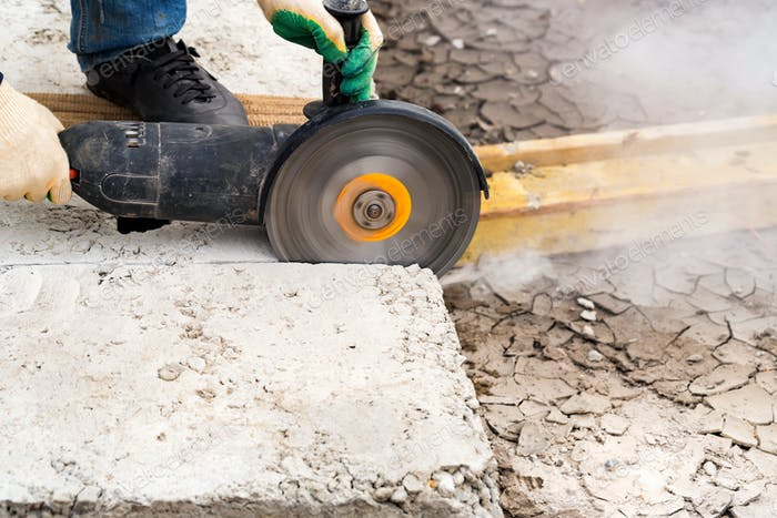 Close up worker cuts concrete with circular saw