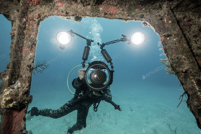 Photographer's video lights illuminate an opening in the Papa Doc shipwreck