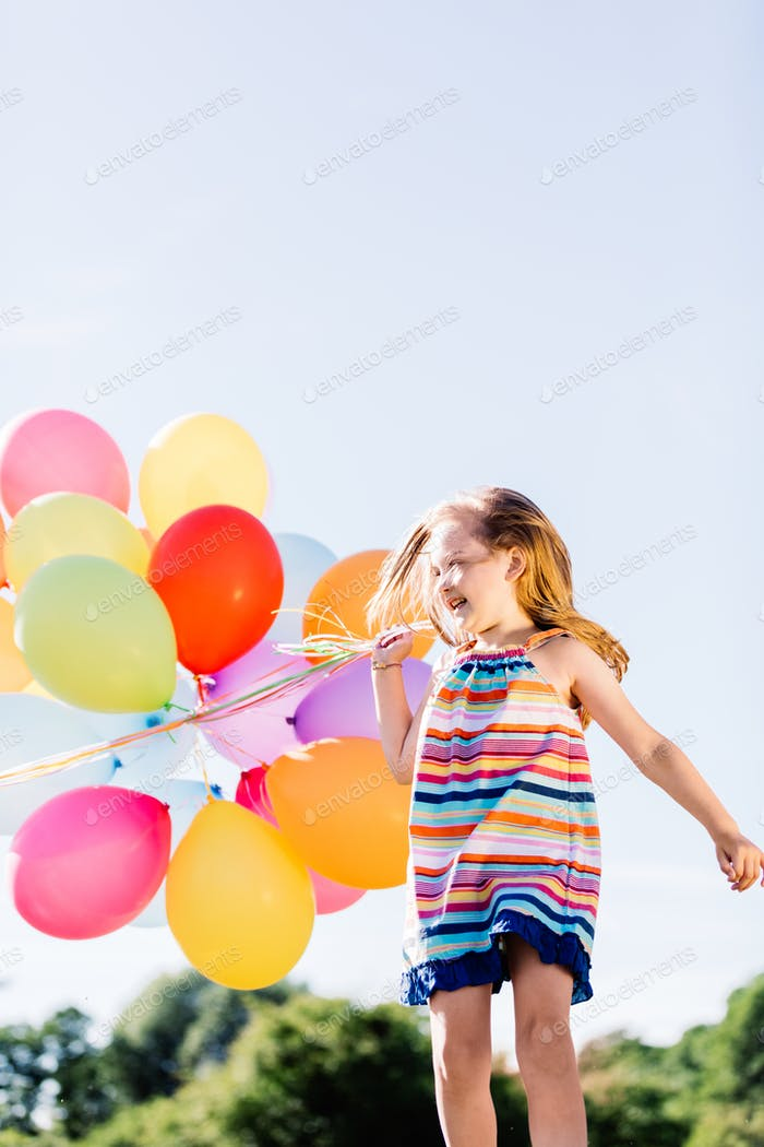 Happy girl running with a bunch of colorful balloons.