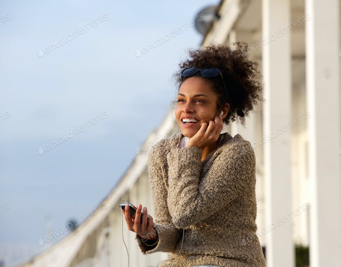 Happy young woman listening to music on mobile phone