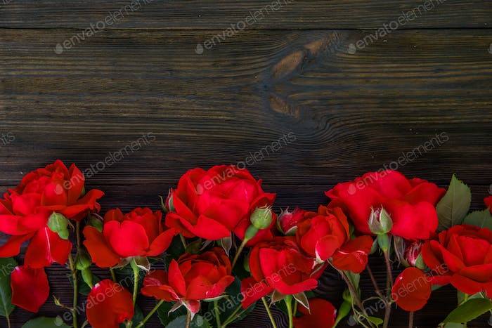 Romantic background with red rose on wood table, top view