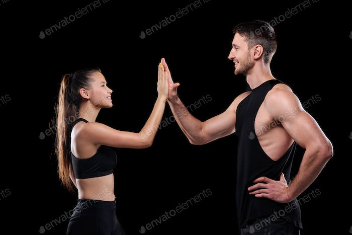 Young sporty dates smiling at each other while making high five gesture