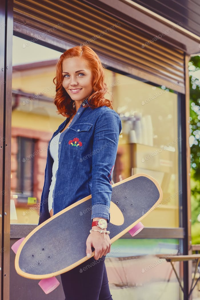 The attractive redhead female holds Longboard.