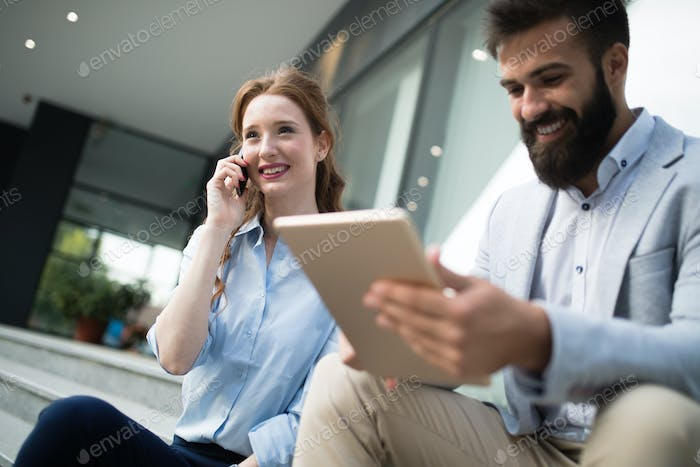 Smiling business man and woman chatting outdoor