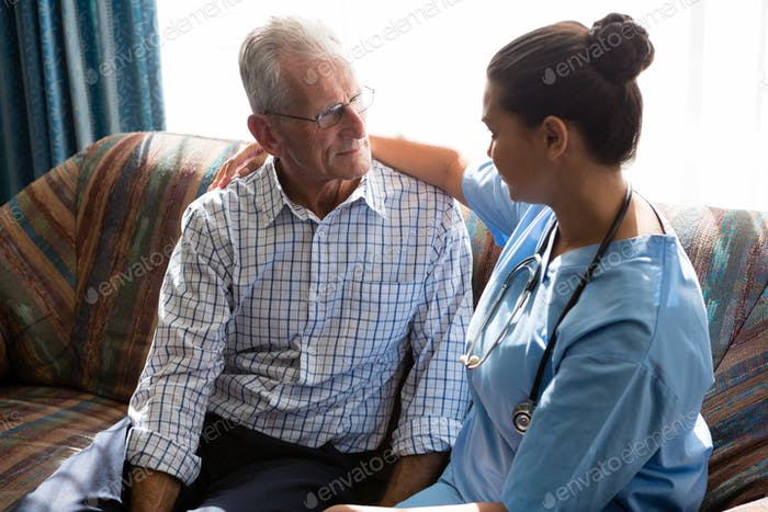 Doctor consoling senior man while sitting on sofa