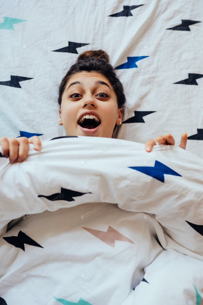 Closeup of Lovely young Woman Lies in Bed Covered with Blanket