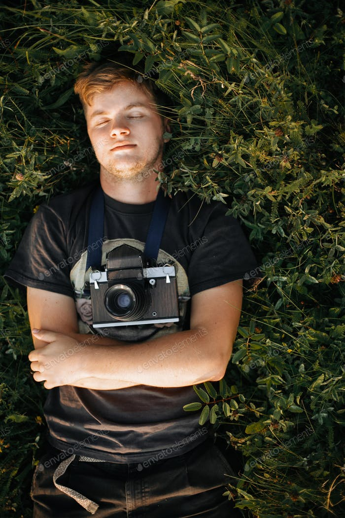 Stylish hipster man with film photo camera lying in green grass and relaxing in sunny meadow
