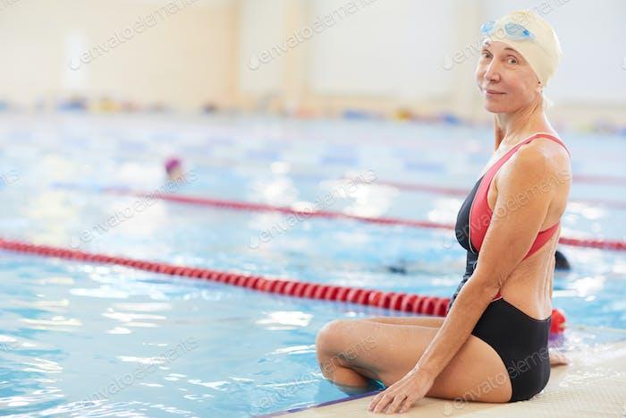 Smiling Senior Woman Sitting by Pool