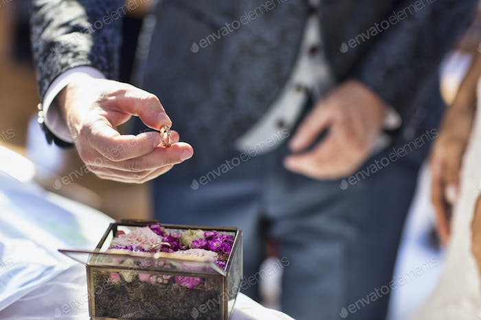 close up of a groom s hand picking up the wedding ring from a casket.jpg