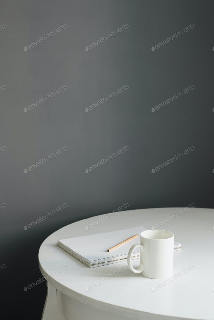 coffee cup with sketchpad and pencil on white wooden table