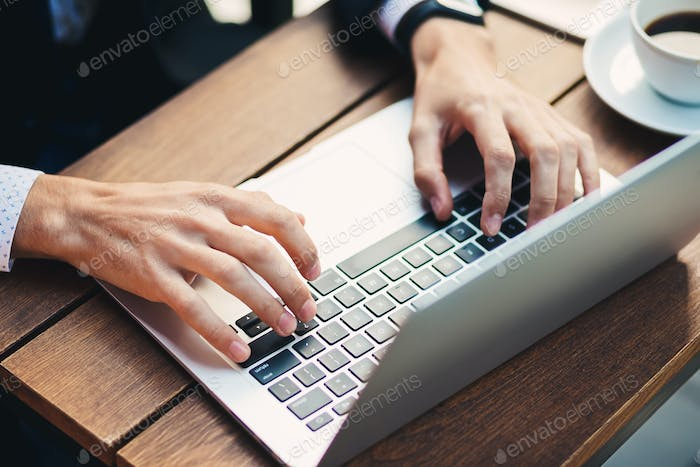 Close-up man hands with accurate manicure, typing on laptop
