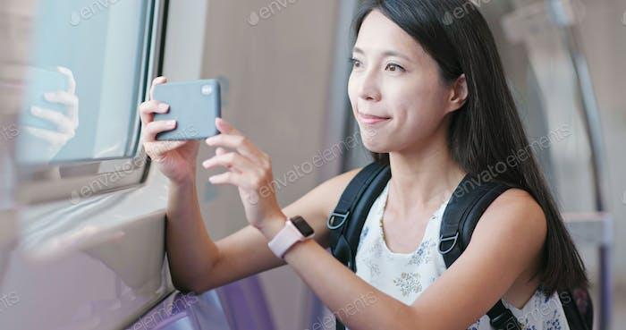 Woman taking photo with cellphone on Taipei city metro