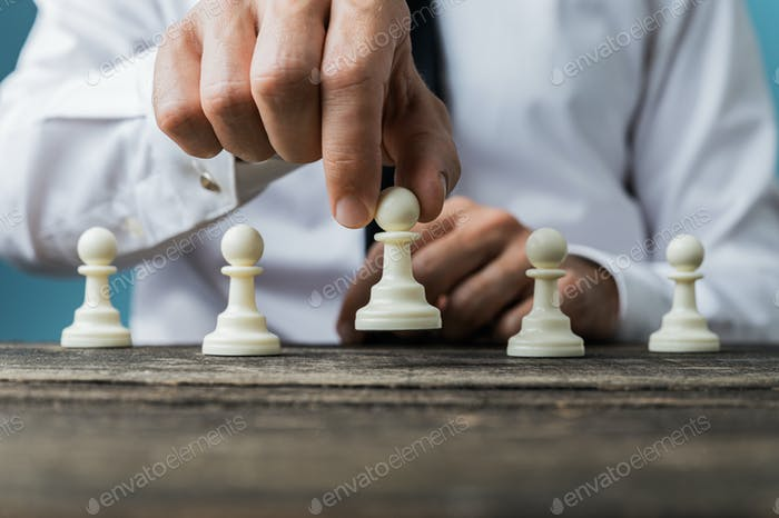 Businessman positioning white pawn chess piece in front of the o
