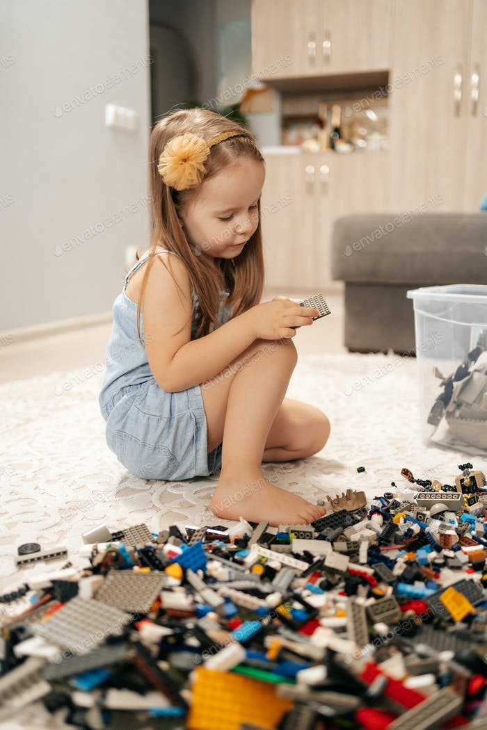 Cute girl playing lego at home