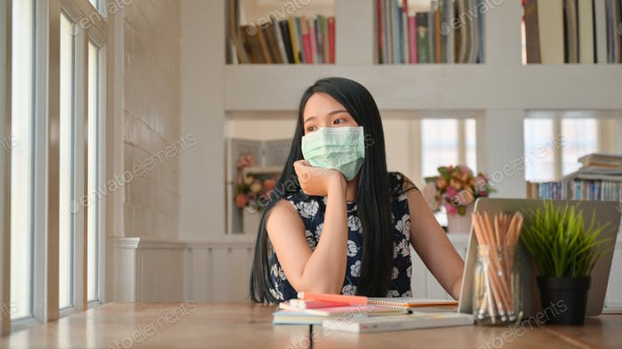 Female students wear a mask and look out the window,coronary virus or Covid-19 concepts.