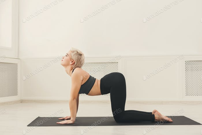 Young woman practicing yoga, Bitilasana exercise