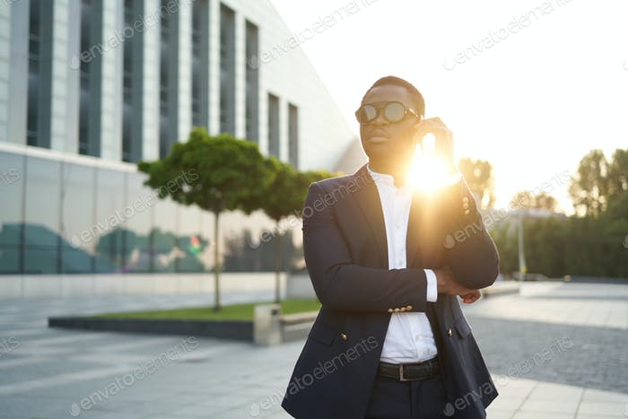 African business man talking on his phone against cityscape