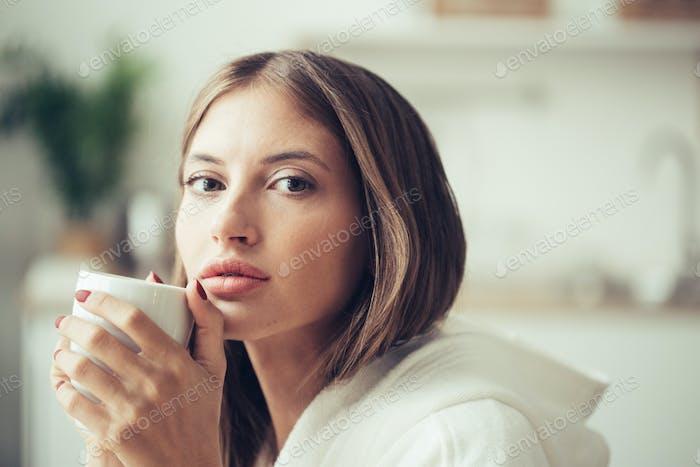Mädchen mit weißer Tasse in den Händen. Casual Frau Porträt mit trinken Tee oder Kaffee weiblichen indors Hause