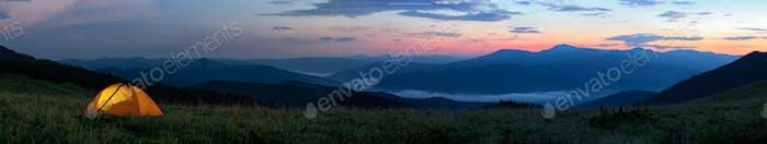 Orange Touristenzelt von innen beleuchtet steht in Bergen über Wolken