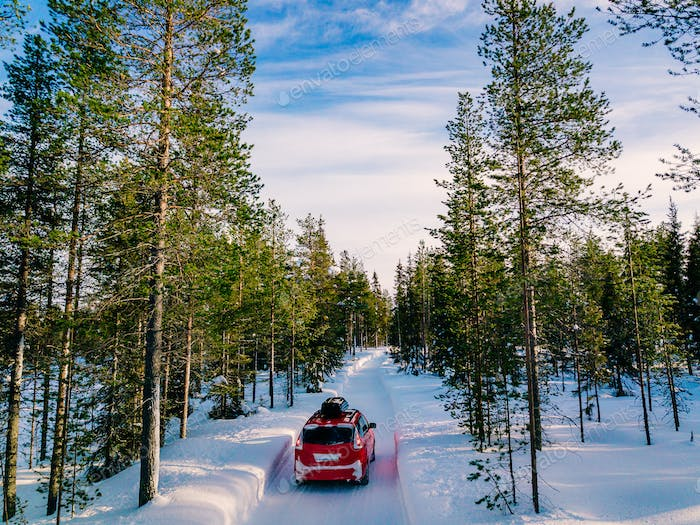 Red car with roof rack driving on snow forest road in winter