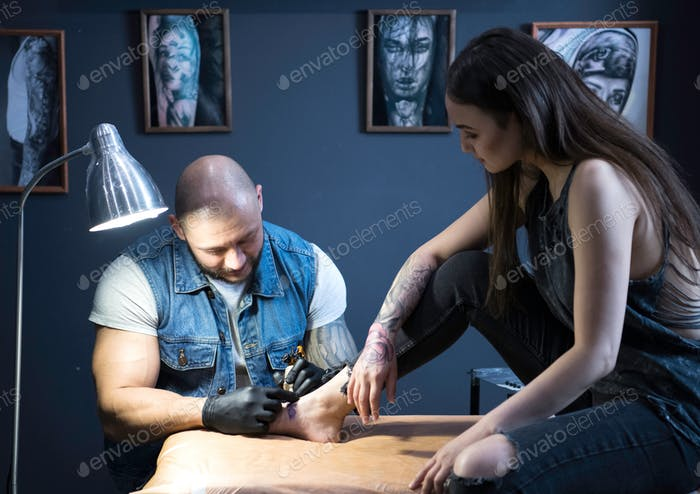 man in black gloves tattooing leg of the beatiful girl sitting o