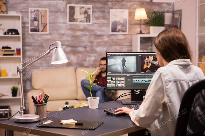 Creative female videographer working on a movie using her home computer