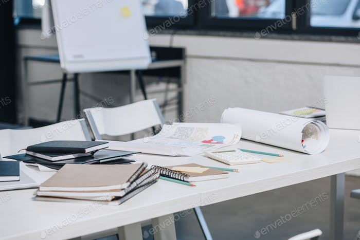 documents, notebooks and blueprints on table in office