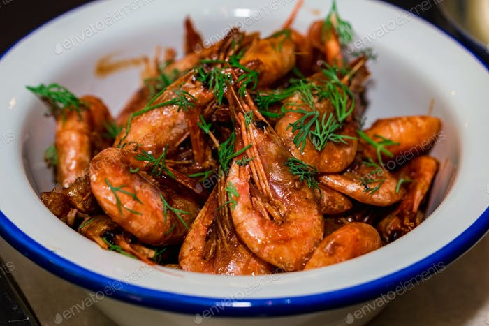 Prepared shrimps with dill in bowl on table close