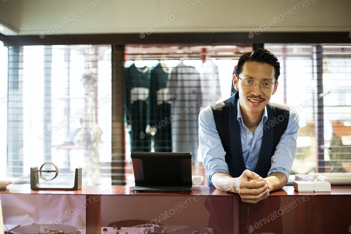 Japanese salesman standing at counter in clothing store, smiling at camera.