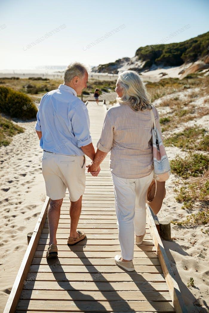 Senior white couple walking along wooden promenade on a beach holding hands, full length, back view