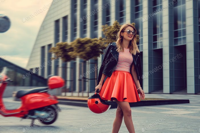 Blond female in red skirt going away from red moto scooter.