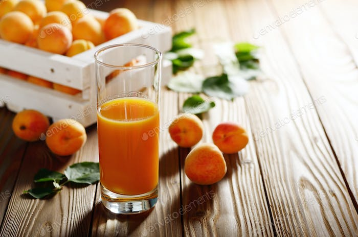 Apricot smoothie in glass on wooden table with crate at backgrou