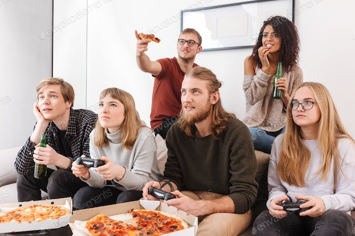 Friends playing video games on sofa, eating pizza and drinking beer