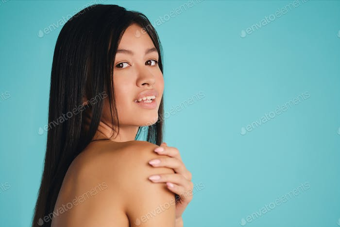 Beautiful Asian brunette girl happily looking in camera over colorful background