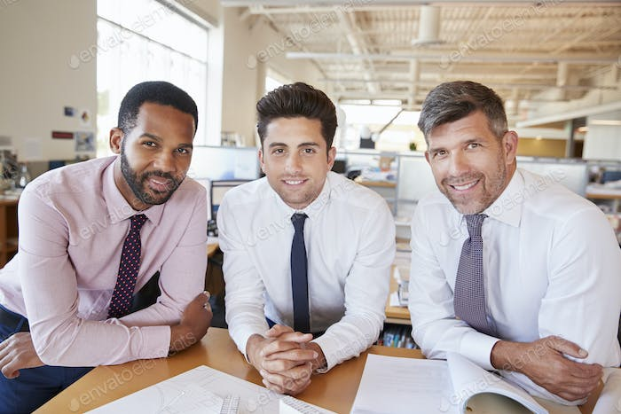 Three male architects looking to camera in open plan office